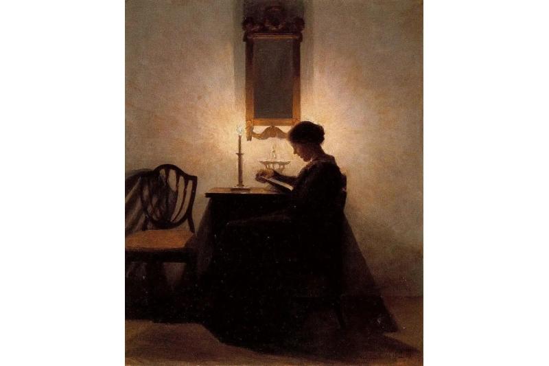 Mujer leyendo a la luz de unas velas